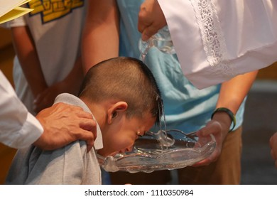 A Asian boy is being baptized. The father wears a white suit. His hand is holding a glass of water and pouring water on the boy's forehead.
