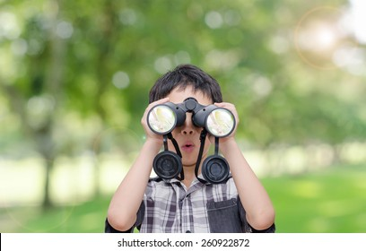 Asian boy with binoculars in garden