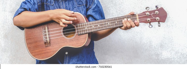 Asian boy Black birth marks on hand Wearing shirt jeans aged 5-6 Play ukulele cool gesture Passionate love in music empty space Old cement wall Child Development Concept