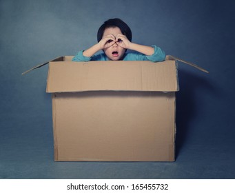 Asian boy in box looking through imaginary binoculars