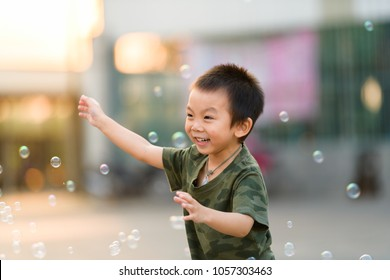 Asian boy in camo t-shirt playing with soap bubble outdoors