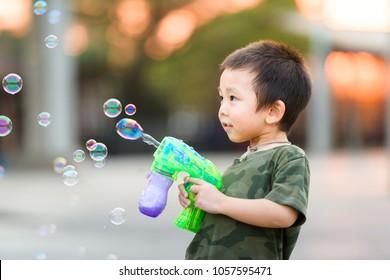 Asian boy in camo t-shirt playing soap bubble outdoors with soap bubble gun