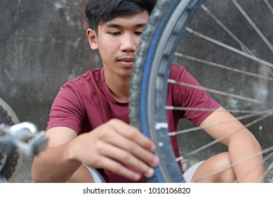 Asian boy checking a bicycle tire.