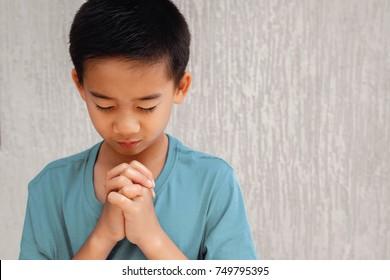 asian boy child praying with eyes closed, christianity faith concept, World Day of Prayer,international day of prayer