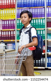 Asian boy chooses stationery in the submarket. The schoolboy holding a trolley.
