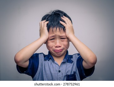 Asian boy crying over dark background