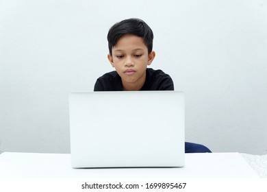Asian boy doing online study working on the computer at home