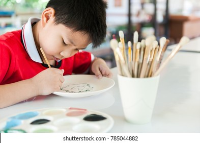An asian boy drawing and painting water colour on a plate at a workshop