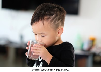 Asian boy is drinking in clear glass.
