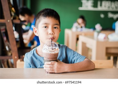 Asian boy drinking cold chocolate in the restaurant.Ice drinking menu in the cafe.Portrait Asian kid.