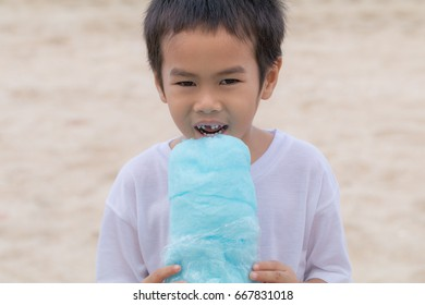Asian boy eating candy floss on the beach in summer