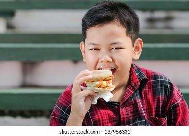 asian boy eating muffin sandwich