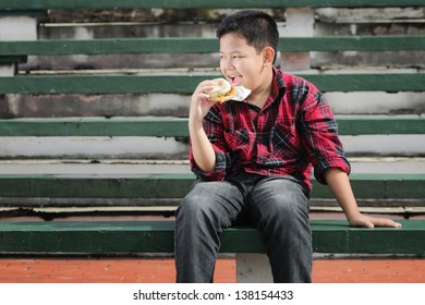 asian boy eating muffin sandwich on a green concrete bench