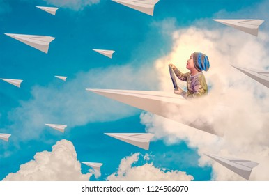 Asian boy enjoys driving a paper plane on the blue sky heading to the horizon. The concept of business leadership, leading the organization to goals, learning and imagination.