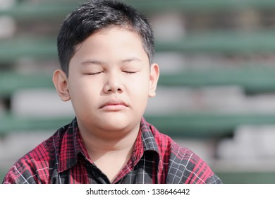 asian boy with eyes closed facing the sunlight