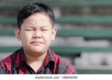 asian boy with eyes closed tight facing the sunlight