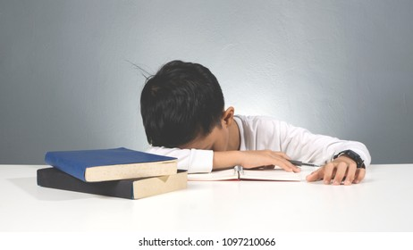 Asian boy fall asleep during study. Tired pupil fell asleep while studying on table with books.
