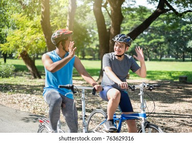 Asian boy with friend ride a bike/bicyle at outdoor green park in summer say hi/bye each other