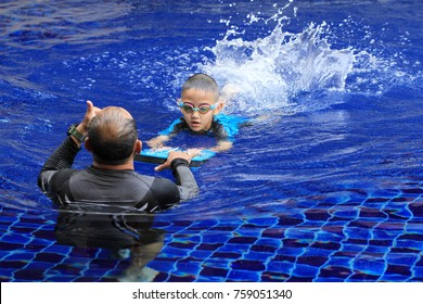 Asian boy gets swimming lessons from coach