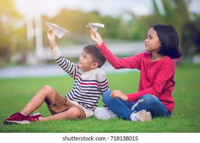 asian boy and girl enjoy with paper plane in the park
