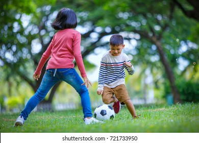 asian boy and girl enjoying with soccer game at outdoor