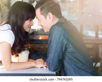 Asian boy and girl in love together sitting and flirting in summer at cafe with beautiful flare light, for Valentine, wedding and love concept