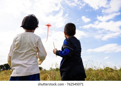 Asian boy and girl playing on the grass field on blue sky background.Happy little children flying kite.Brother and sister relaxation in outdoor park with family.