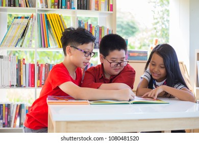 Asian boy and asian girl are reading together with happiness in their kindergarten classroom, kid education and diversity concept