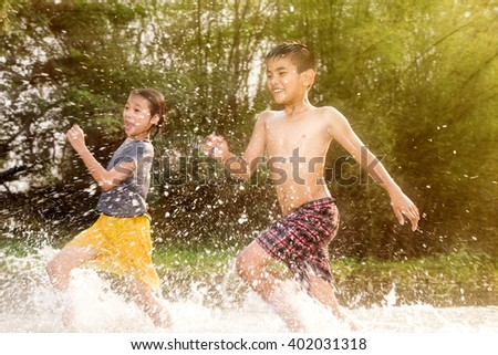 Asian boy and girl running on the river in sunset so happy