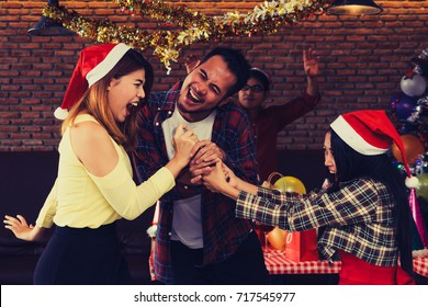 Asian boy and girl scramble for microphone to sing in Celebration party Christmas and Happy New Year.