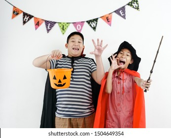Asian boy and girl with witch costume, halloween concept.