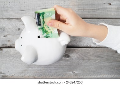 Asian boy hand inserting a twenty dollars bank note into white piggy bank  against wooden grey background
