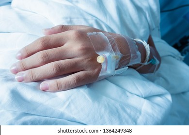 Asian boy hand of a patient with medical drip or IV drip in hospital,Patient with drip receiving a saline solution.patient lying on bed in hospital