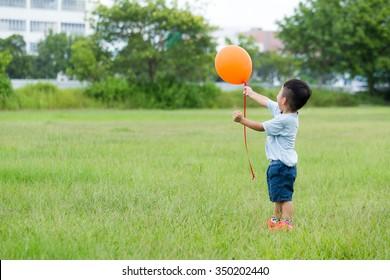 Asian boy hold with the orange ballon