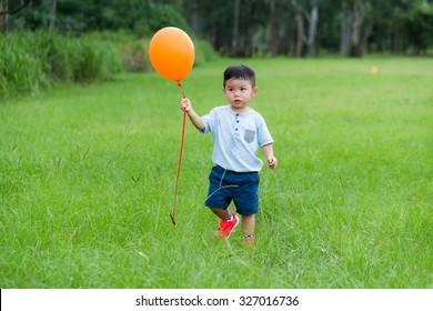 Asian boy hold with orange balloon