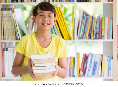 Asian boy is holding book. Happy Children with book in library on elementary school lesson. education concept