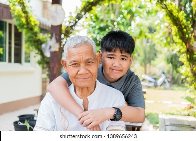 Asian boy hugging living with retired grandfather. Nephew or grandson playing smile together looking at camera in home outdoor, Happy family members relationship / Father and Dad Day concept.