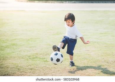 Asian boy kicking football on the field