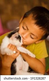 Asian boy kissing a cat.