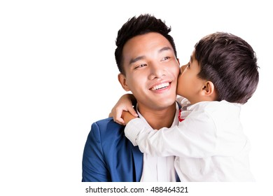 Asian boy kissing his dad isolated on white background.