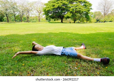 Asian Boy lay on the grass feel relax