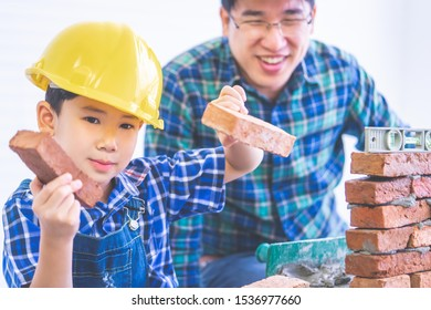 Asian boy is learning how to build a brickwall from his construction builder father, Engineer father is teaching his son in house repairing for family lifestyle concept.