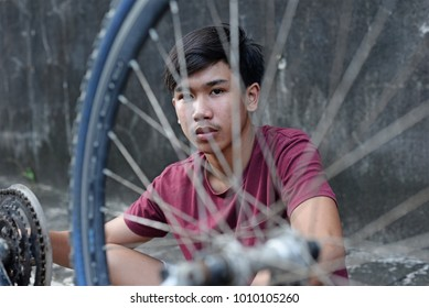 Asian boy looking through spokes of a bicycle tire.