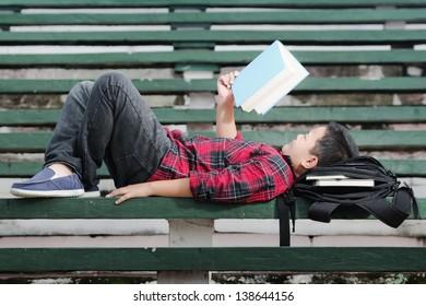 an asian boy lying on a green concrete bench, reading a book