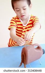 Asian boy making a horse from reuse bottle