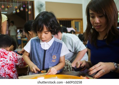 Asian boy and mum are chopping vegetable at school in Bangkok, Thailand. August 11, 2013