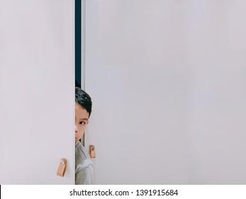 Asian Boy Peeking Through Large White Door