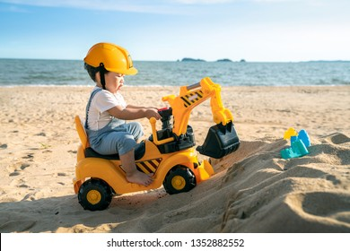 Asian boy play a excavator toy on the beach, this photo can use for kid, summer, travel, and education
