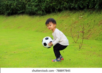 asian boy play football in the park. Kid hold ball in grass field.