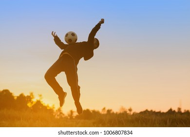 Asian boy player football soccer in the sunset background